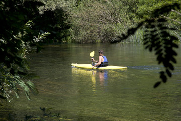 Young adult man kayaking down the river Cetina in Croatia