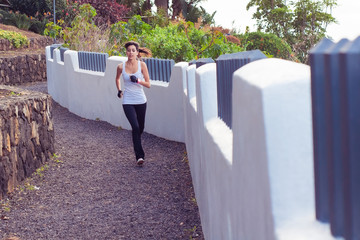 Young woman running through an urban path