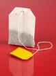 Tea bag on red background