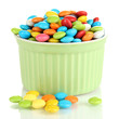 Colorful candies in bowl isolated on white