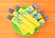 Blue plastic forks wrapped in yellow paper napkins,