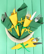 Forks and knives wrapped in green and yellow paper napkins,