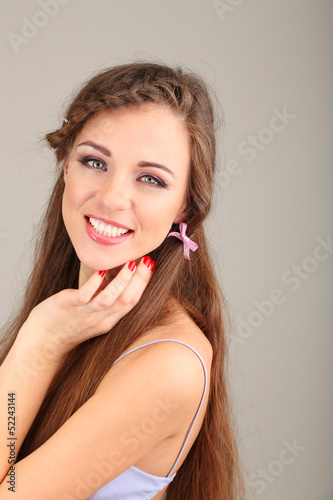 Young woman with beautiful hairstyle on grey background