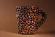 Cup of coffee beans, on brown background