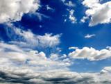 Sommerlicher Himmel mit weißen Wolken und Gewitter-Wolken