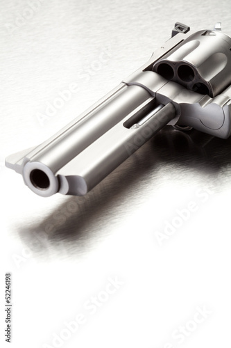 Gun on brushed metal surface