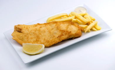 Battered fish and chips with lemon wedge and tartar sauce