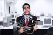 Crazy businessman tied in cable and rope at office