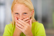 happy preteen girl covering her mouth and laughing