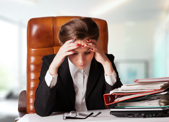 Tensed young business woman holding her head while at work