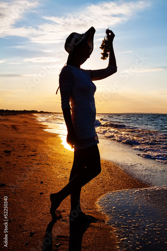 silhouette of sexy girl in hat holding grapes