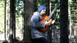 Man playing guitar in the woods leaning against tree/episode 2/