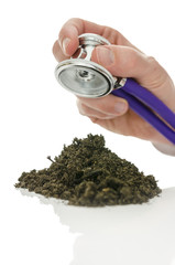 Stethoscope over pile of soil