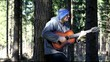 Man playing guitar in the woods leaning against tree/episode 3/