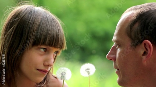 happy father and son blowing dandelion seeds