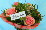 With love note attached to pink roses bouquet