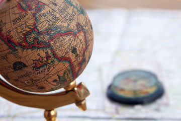 Ancient globe and compass over a map