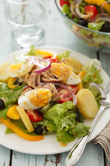 nicoise salad over blue wood background