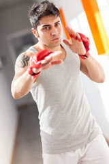 Boxer with red gloves in a gym