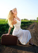 Beautiful blonde girl in long white dress, sitting on suitcase