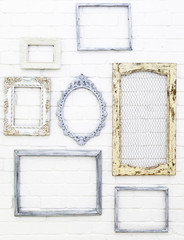 Vintage picture frames on white brick wall background