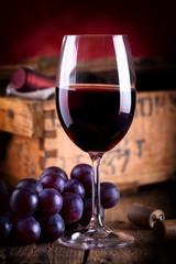 Glas Rotwein vor antiker Weinkiste