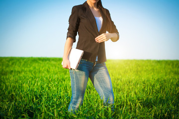 businesswoman in a green field with a laptop. consept