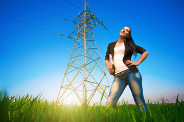 pretty businesswoman in a field with a laptop. power lines