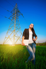 cute woman in a green field with a laptop. power lines