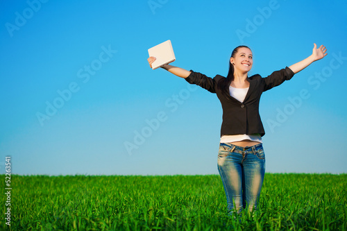 happy businesswoman in a green field with a laptop. summer