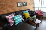 Fototapety Colorful pillows on a sofa with brick wall in background