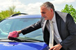 Man wearing suit cleaning a car.