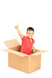 Smiling child in a paper box giving thumb up and looking at came