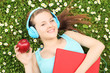 Young female listening music and holding an apple, on a green gr