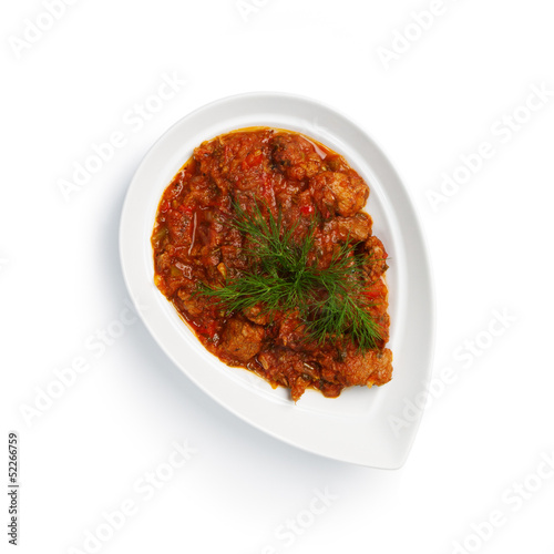 meat in a sauce on a white plate