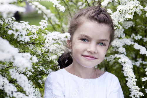 Portrait of beautiful little girl in spring blossom