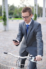 Portrait of young businessman on a bike using mobile phone