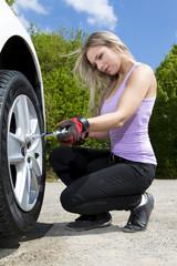 Blondine mit Drehmomentschlpssel in der Hand wechselt die Reifen