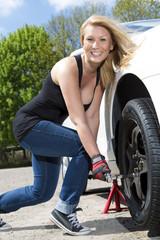 Frau wechsel draußen die Reifen und lächelt dabei zum Betrachter