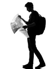 young man silhouette backpacker reading map
