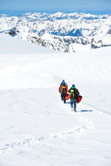 A group of mountain hiker walking on the snow into the mountain