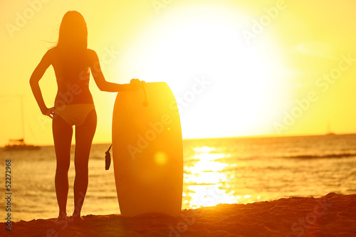 Sunset at summer beach with body surfer woman