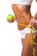 Healthy female body with apple and measuring tape