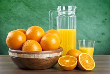 jus d'orange avec des oranges sur la table en bois