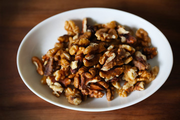 Walnuts, shelled fruit on white plate, food ingredient