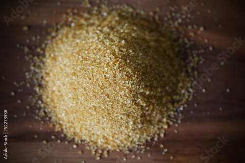Brown sugar from cane, crystals in heap on brown wooden board