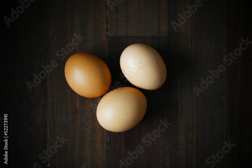 Three chicken eggs on dark wooden surface