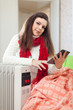 woman reads e-book near  heater