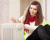 woman warms hands near radiator