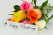 Happy Birthday note and colorful bouquet of roses